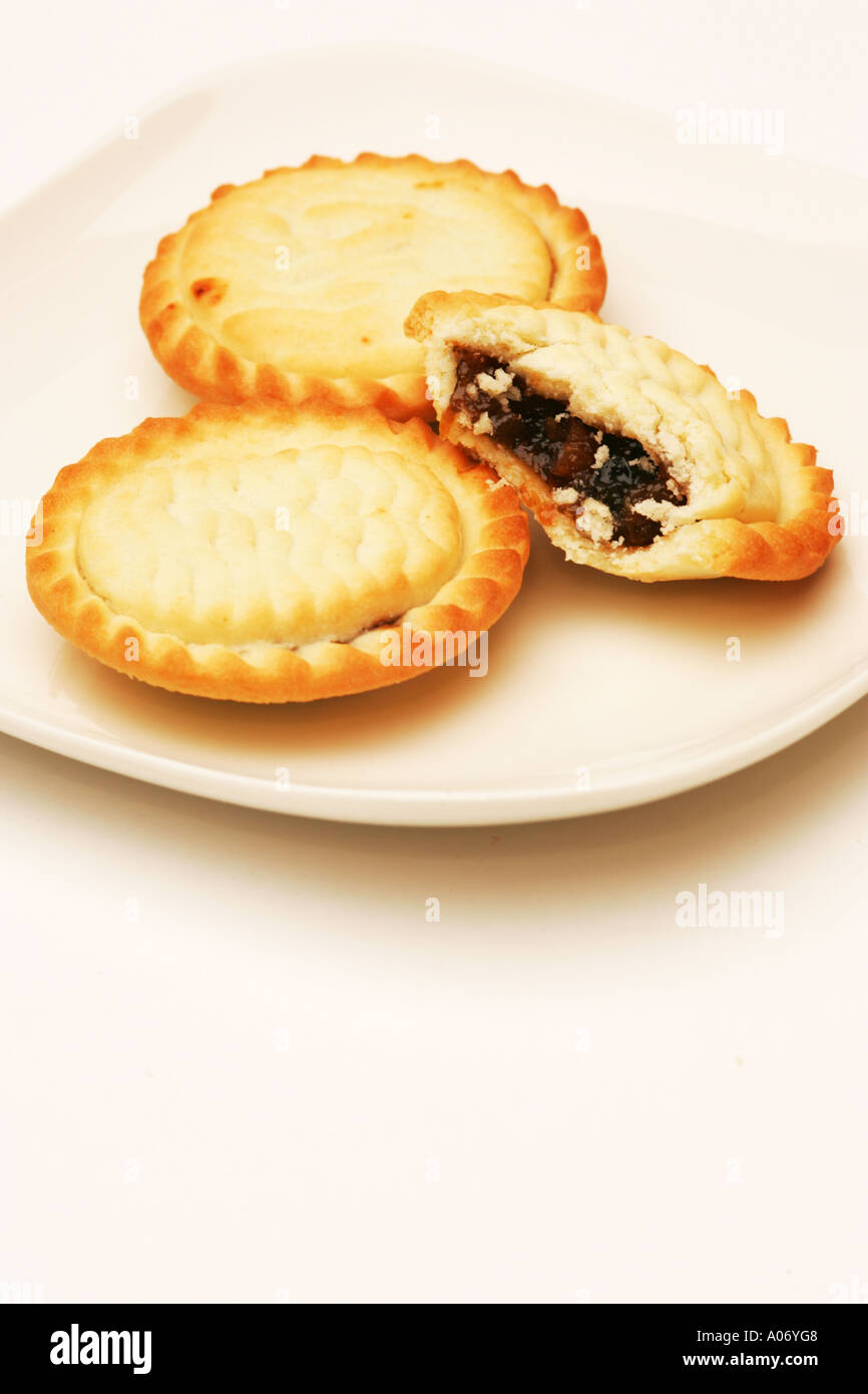 Closeup of a half eaten mince pie on white plate with two 2 full pies traditional Xmas Christmas snack food in Britain UK  sc 1 st  Alamy & Closeup of a half eaten mince pie on white plate with two 2 full ...