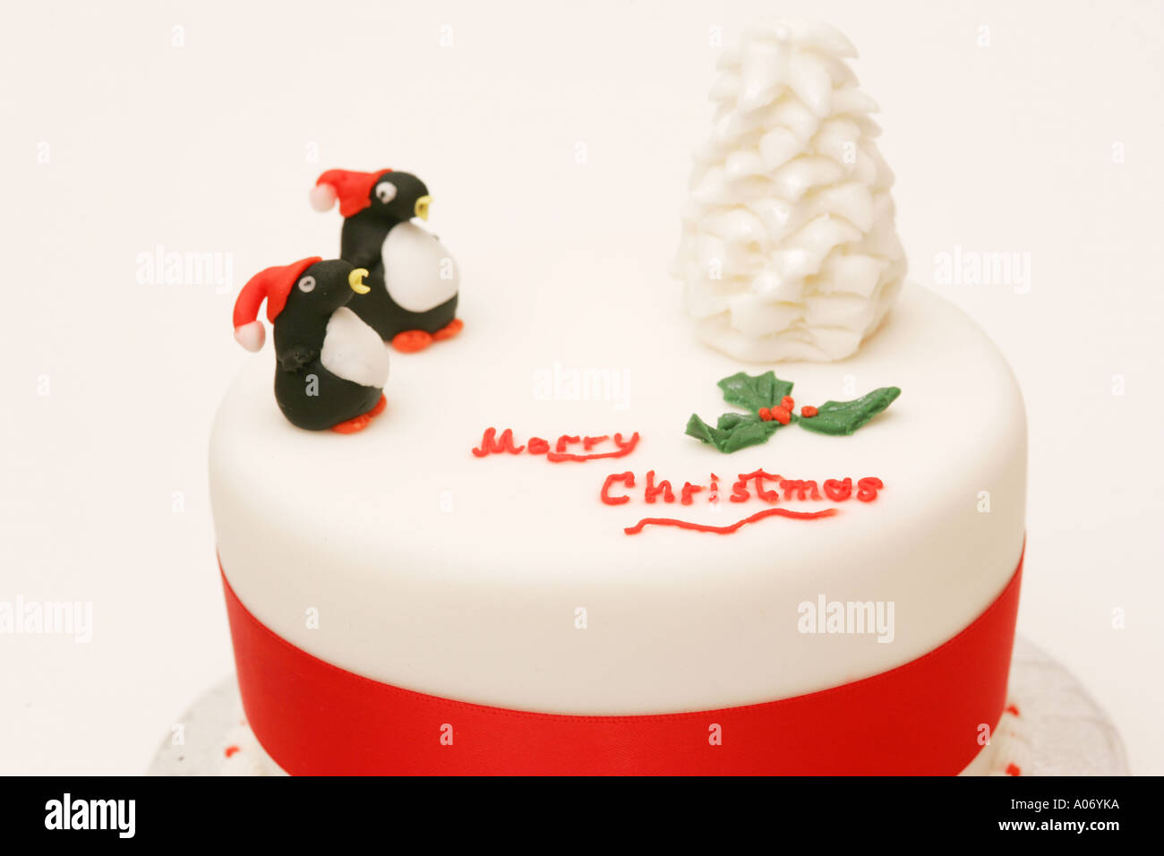 closeup traditional seasonal festive british xmas cake with novelty iced tree and penguin decorations merry christmas - British Christmas Cake Decorations