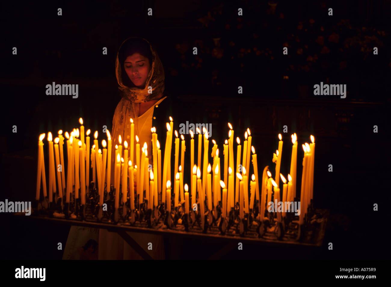 A woman lighting prayer candles inside a Catholic Church in Italy. & A woman lighting prayer candles inside a Catholic Church in Italy ...
