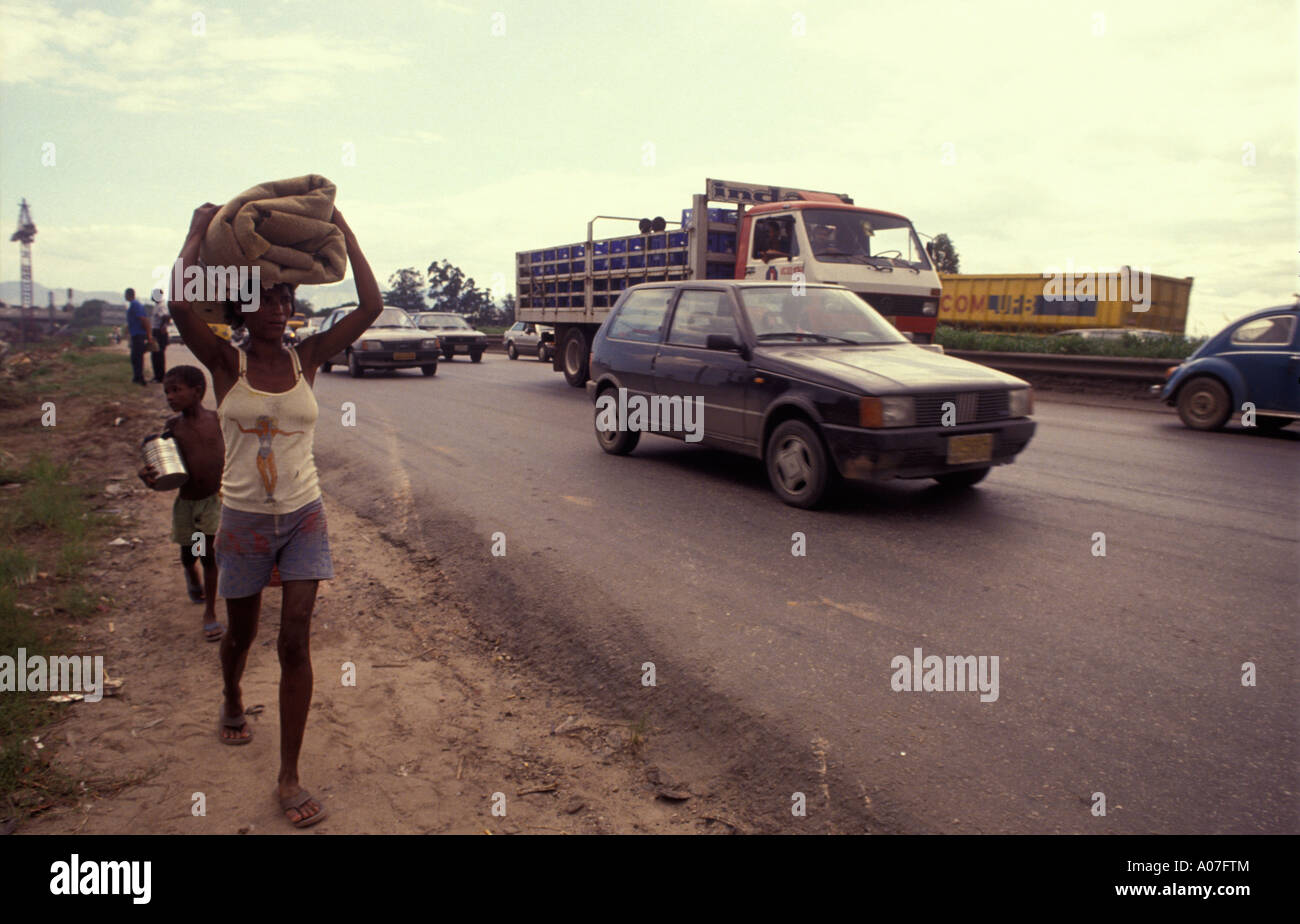 Homeless woman and her son walk besides a road carrying all her stuff Rio de Janeiro Brazil - Stock Image