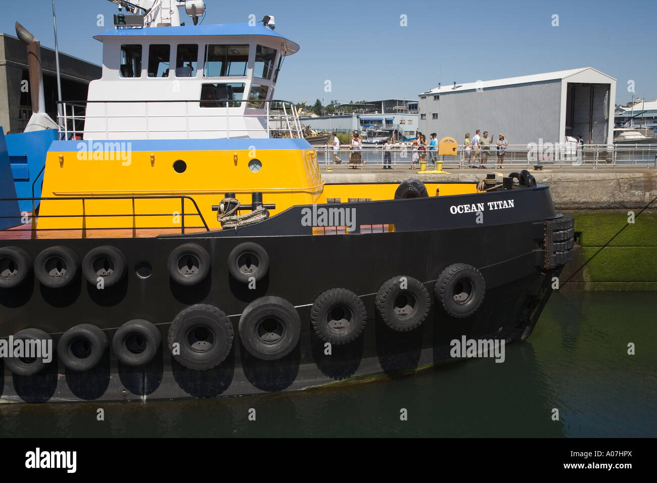 Tugboat protected by car tyres on prow Hiram M Chittenden Lock on the Lake Washington Ship Canal Seattle USA - Stock Image