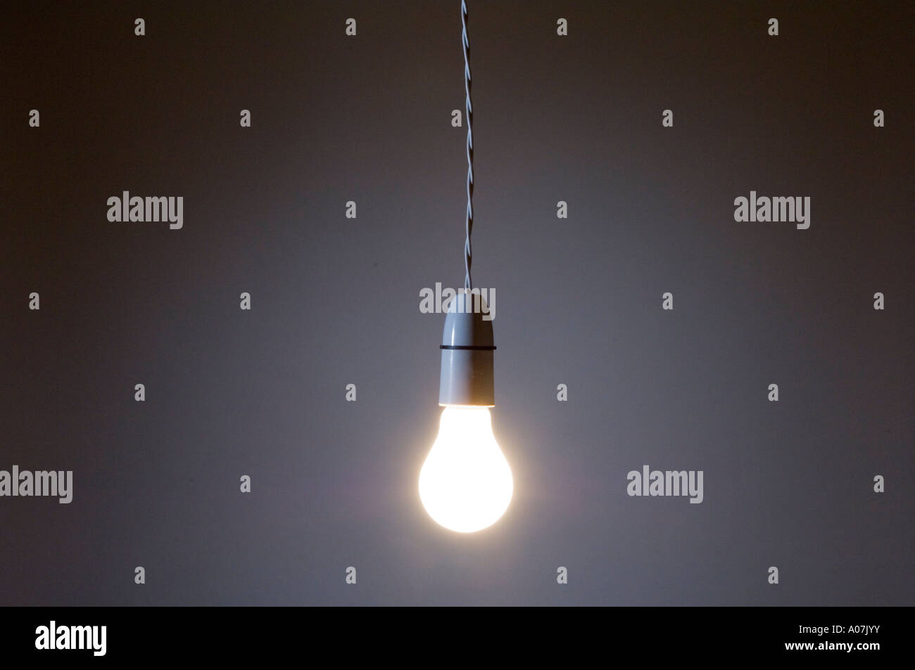 An incandescent lightbulb hanging by a twisted flex wire - Stock Image