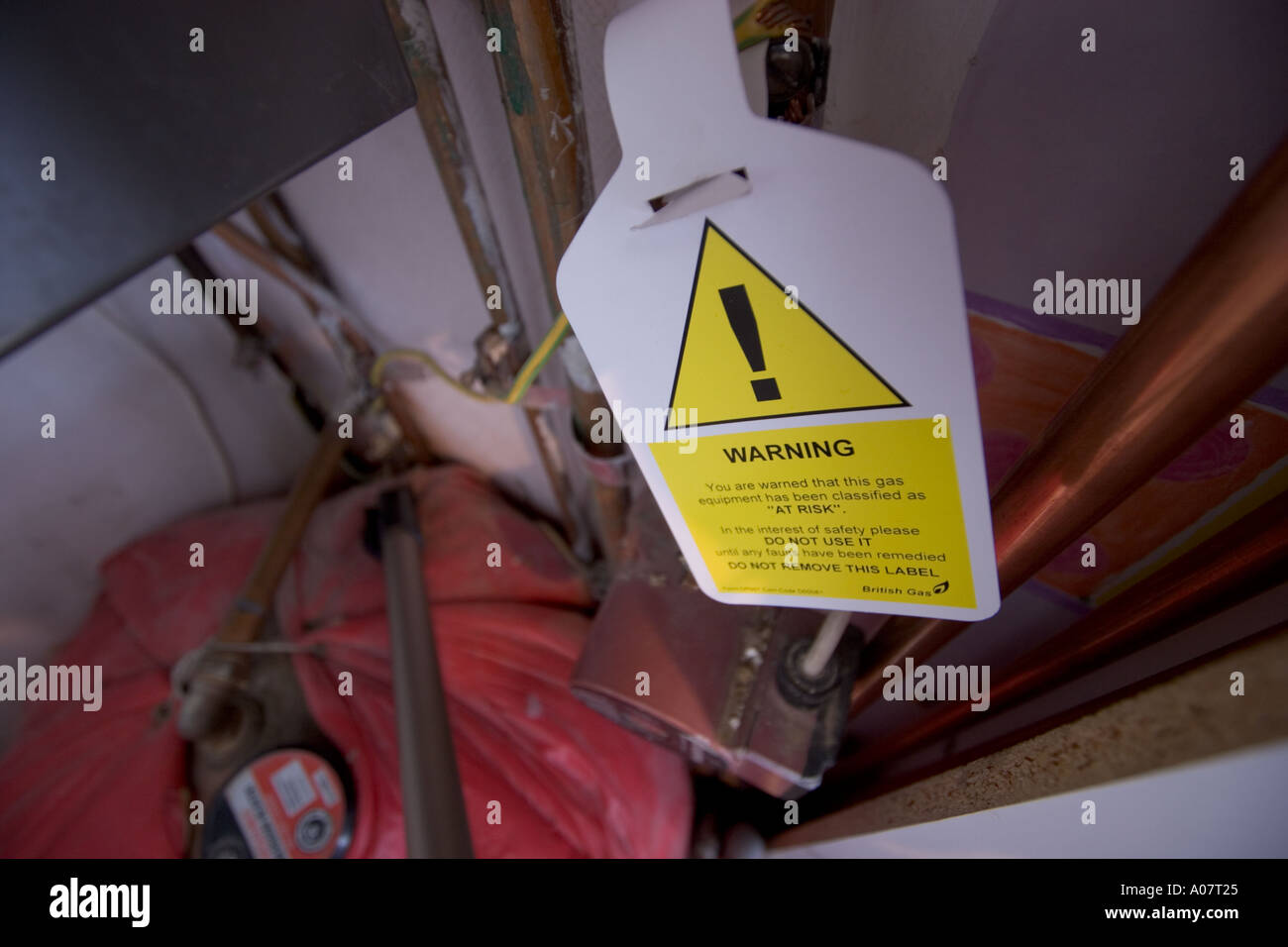 Dangerous Gas appliance household boiler and pipes with sign you are warned that this gas equipment has been classified as at - Stock Image