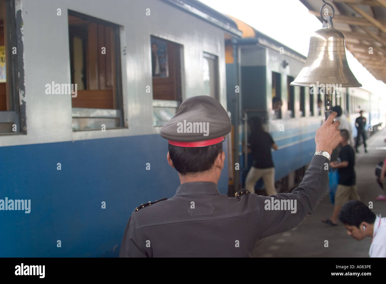 Conductor ring bell to signal departure of train from Thonburi Station Bangkok's southern railway  to Kanchanaburi - Stock Image