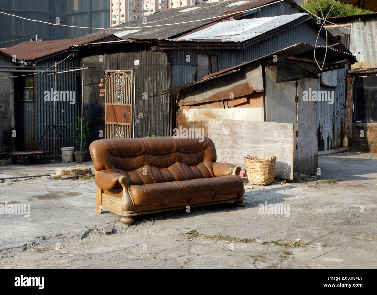 Old sofa, building and squatters shack on the back streets of Taipa Island, Macau, South China - Stock Image