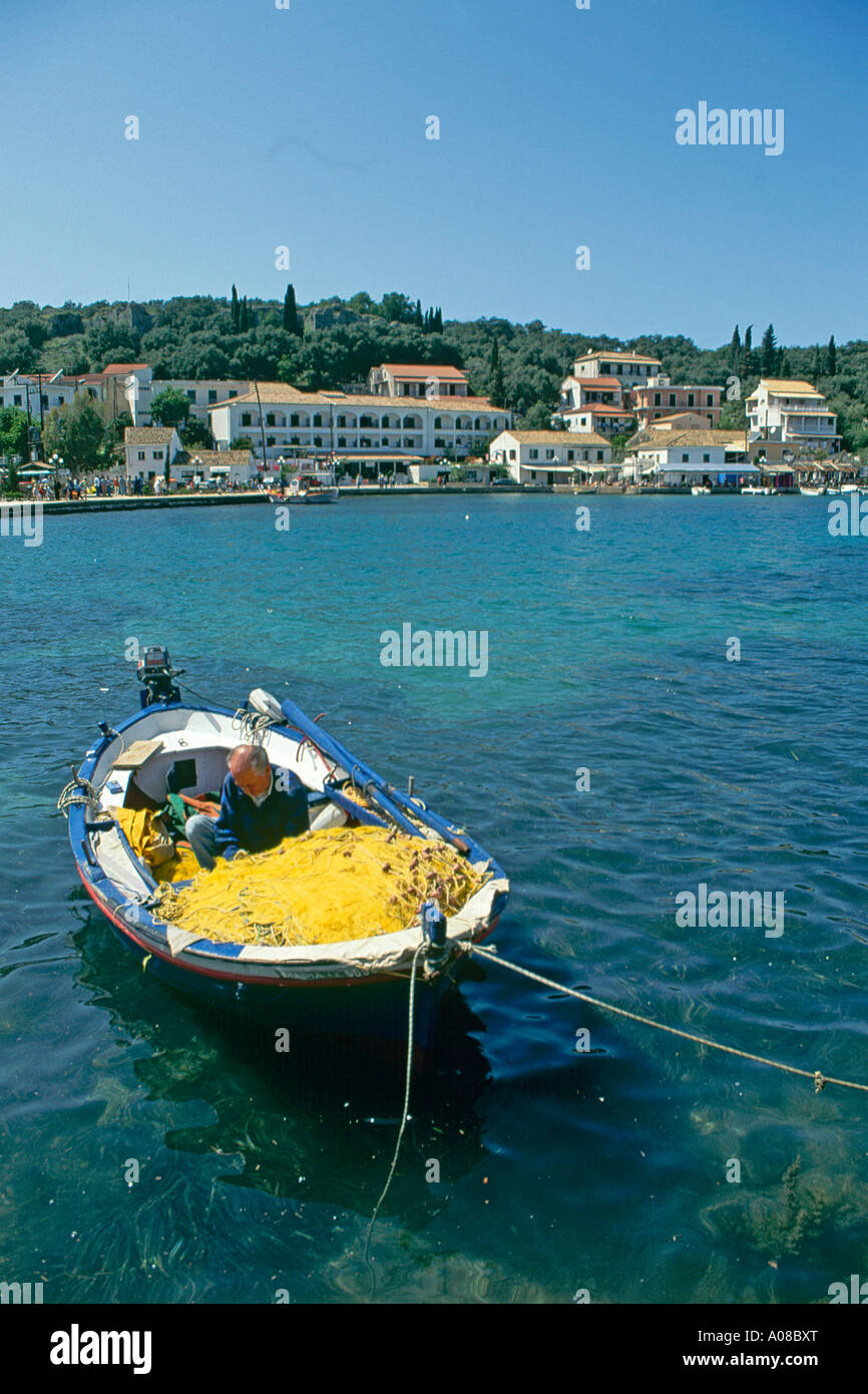 A fisherman working on his nets on the open deck of his small boat tied up in the harbour at Kassiopi - Stock Image