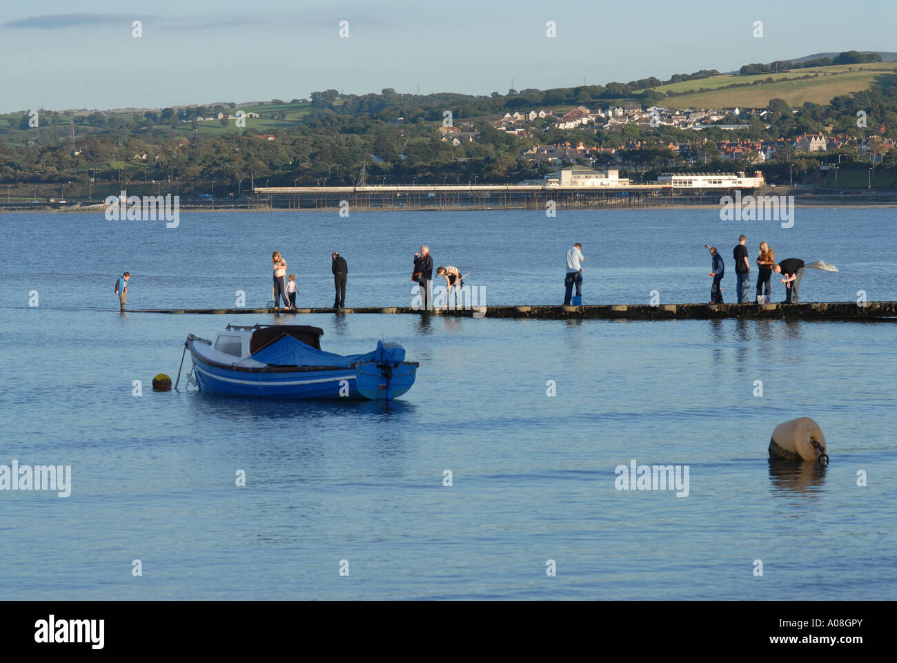Tourists Fishing and Moored Boat Harbour Rhos on Sea North East Wales - Stock Image