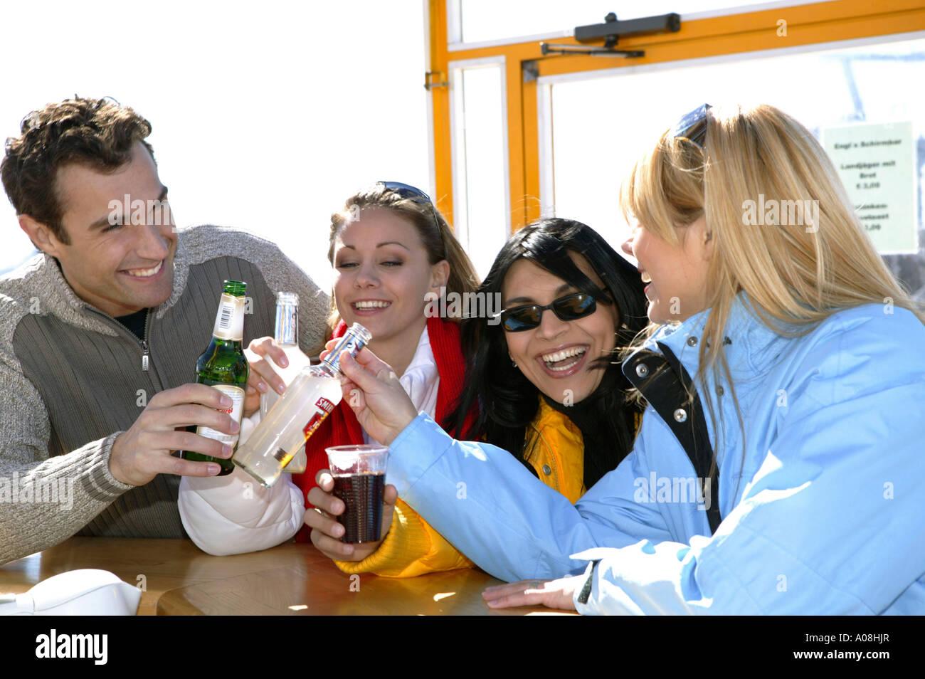Junge Leute beim Apres-ski im Winterurlaub, young people at apres ski in winter holiday - Stock Image
