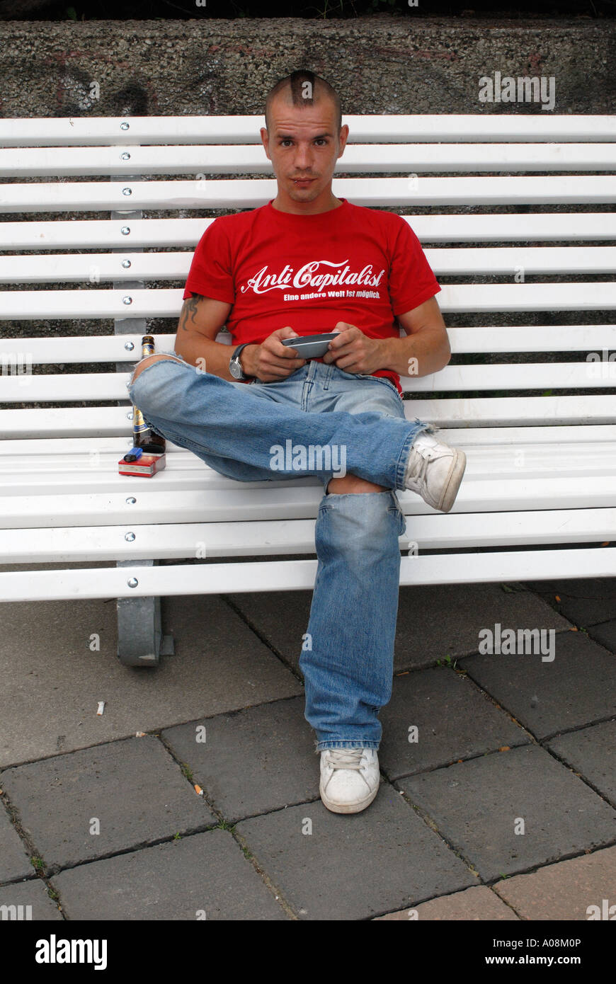Shaven haired man sitting on a park bench wearing an anti capitalist tee shirt - Stock Image