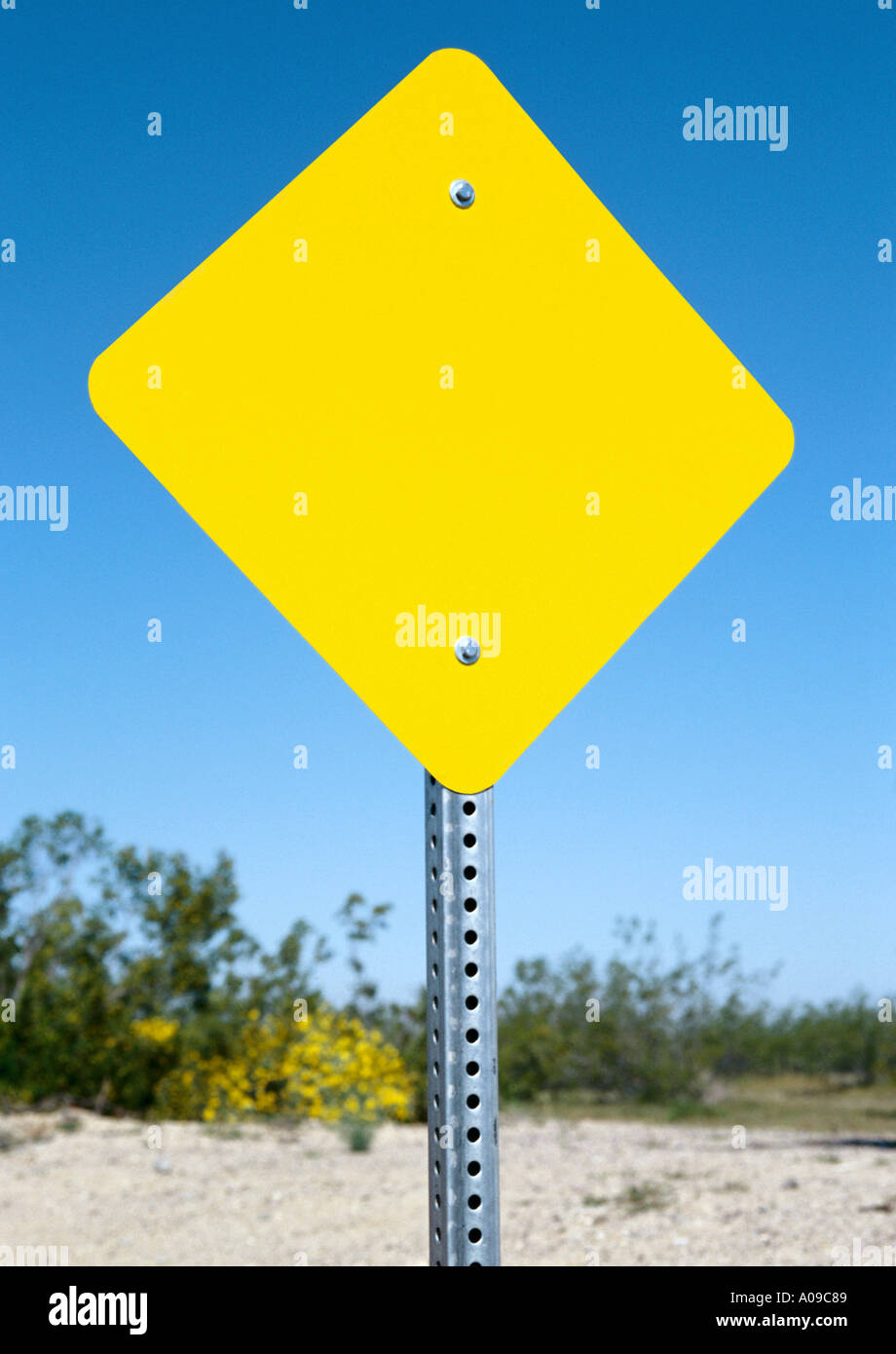 A yellow diamond shaped blank road sign on a metal post ...