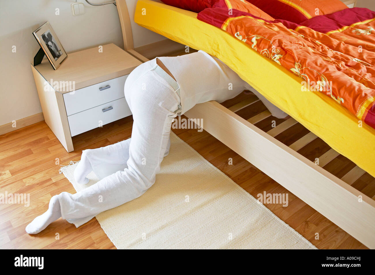 Frau sucht etwas unter dem Bett, woman searching something under the bed - Stock Image