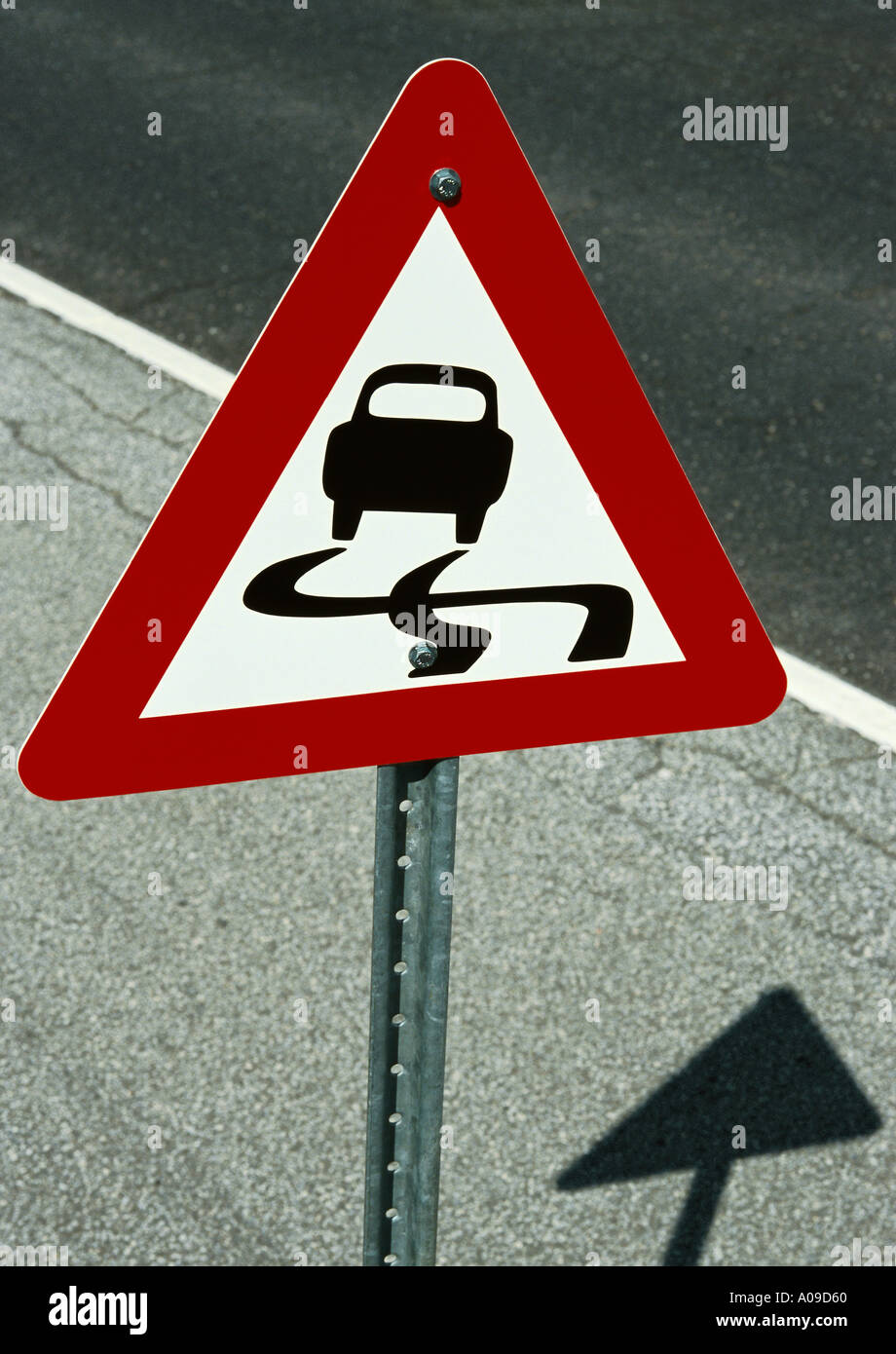A red white and black triangular slippery road sign on a metal post situated on the paved shoulder of a highway - Stock Image