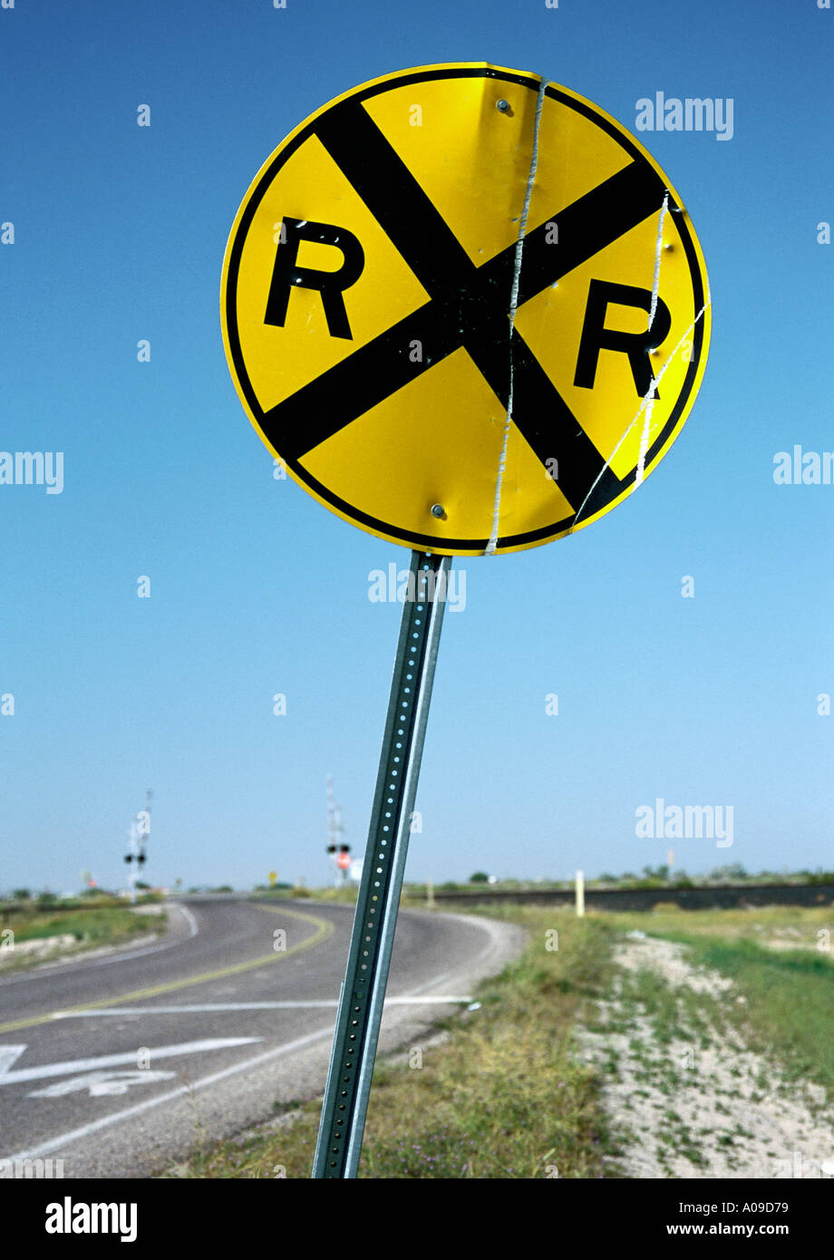 Circular railroad crossing road sign with railway tracks in