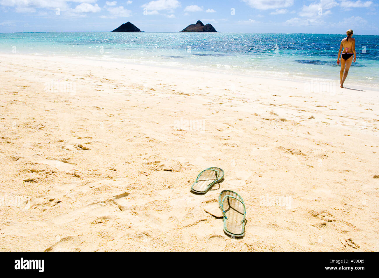 sunbather leaves her flip flop and runs into the surf - Stock Image