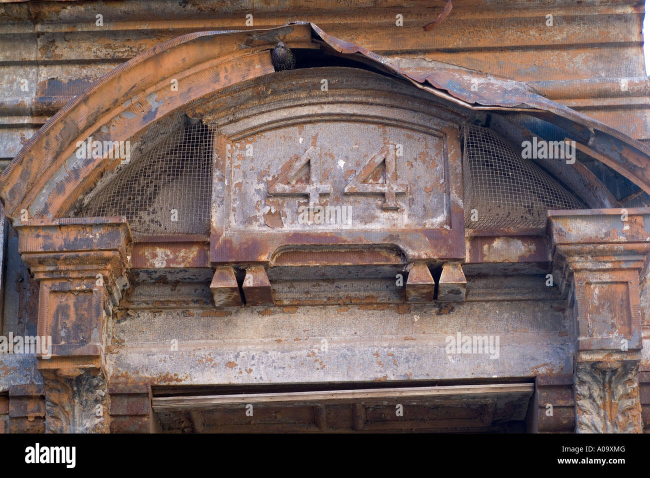 Blighted Industrial building detail with number 44 over doorway - Stock Image