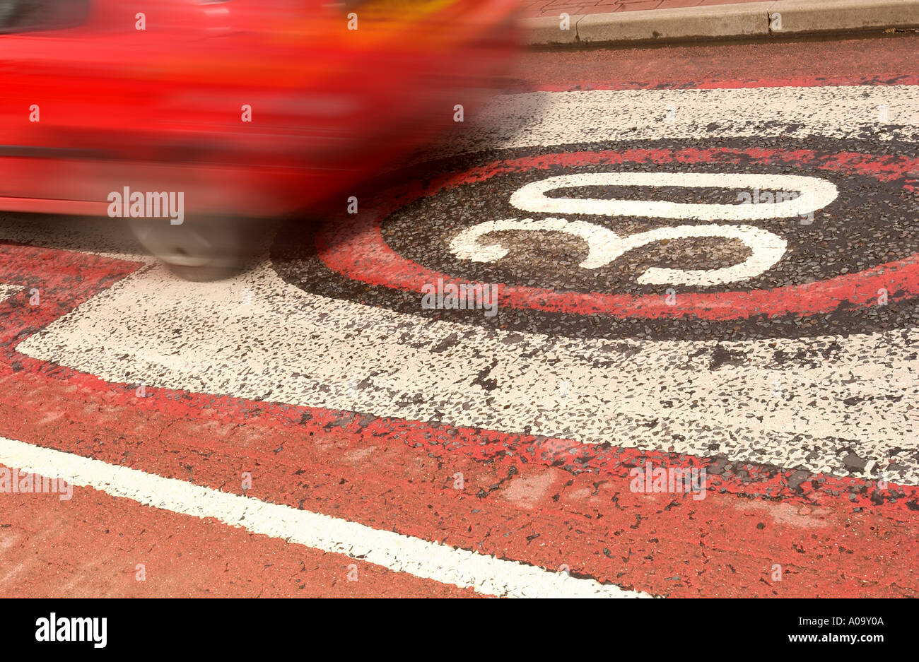 A CAR PASSES OVER A WORN THIRTY MILES PER HOUR SPEED WARNINGS PAINTED ONTO THE ROAD UK - Stock Image