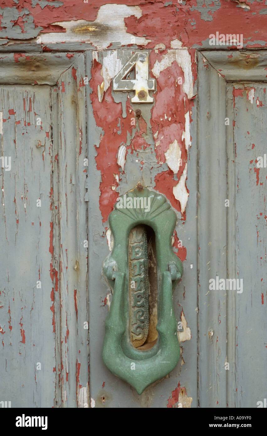Neglected and peeling front door with letterbox and knocker and number four - Stock Image