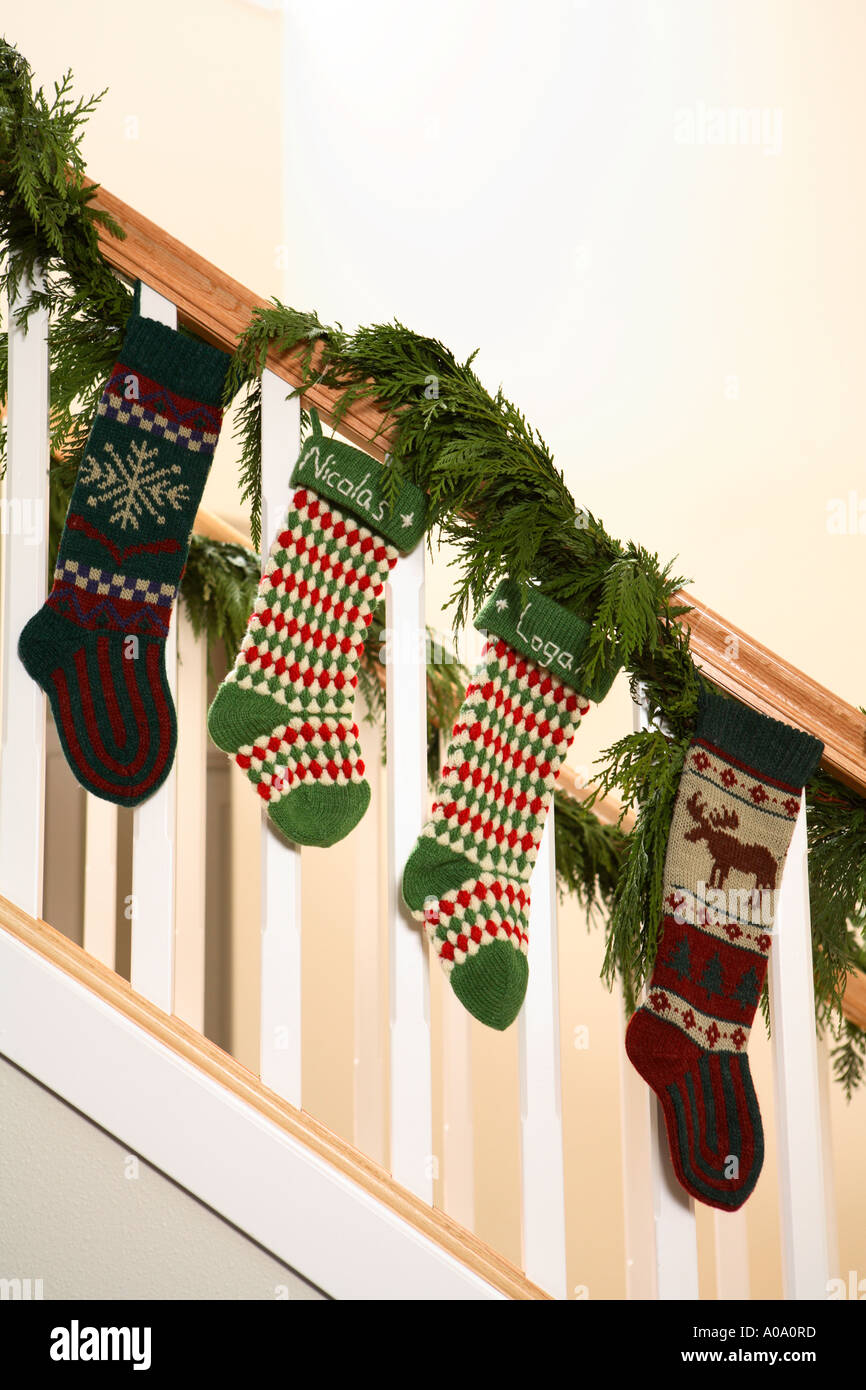 Four knit stockings hanging on stairway rail inside home. - Stock Image