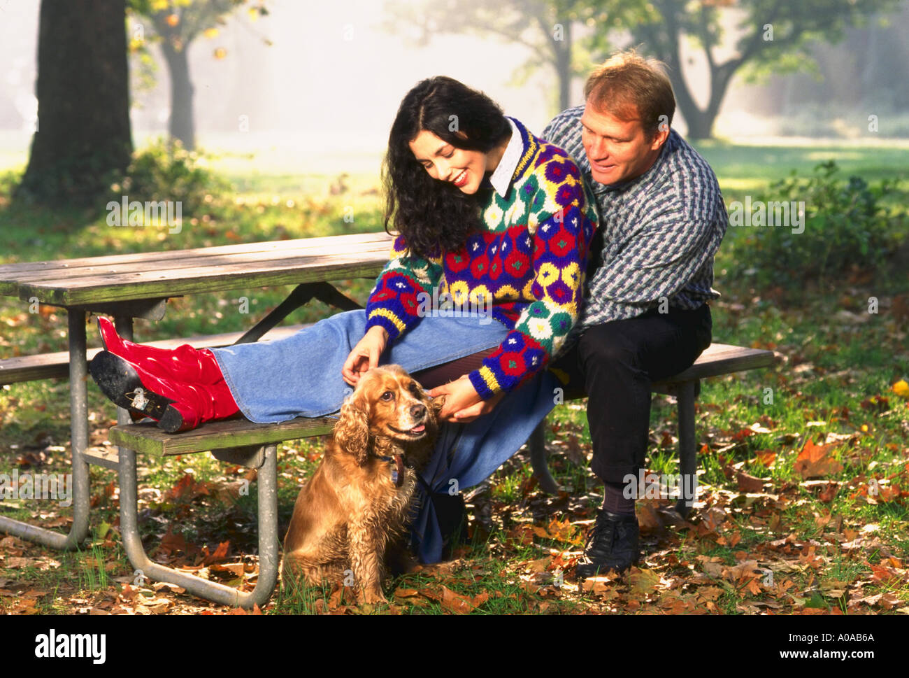 Young couple sitting at picnic table with cocker spaniel dog - Stock Image