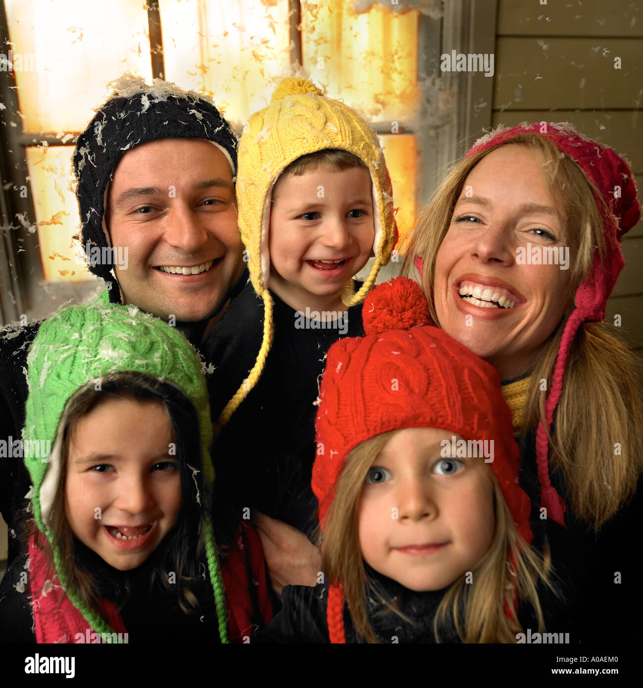 A family poses outside in the snow in front of a home with warmth radiating from the window as well as their expressions. - Stock Image