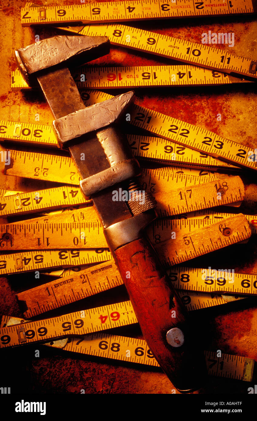 Old monkey wrench and wooden rulers Stock Photo