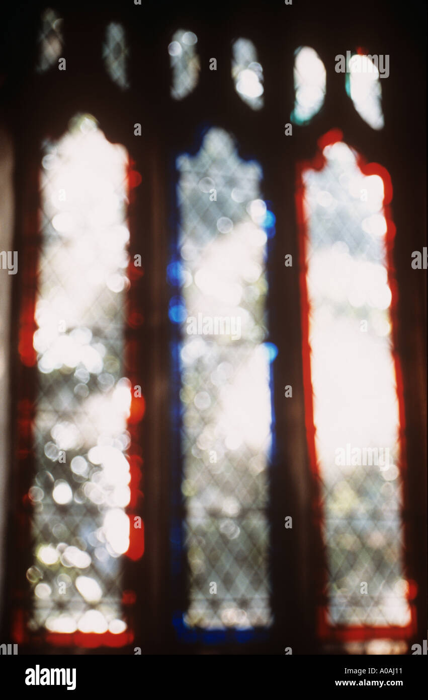 Impressionistic three long church windows with clear leaded diamond panes but fringed with red or blue - Stock Image