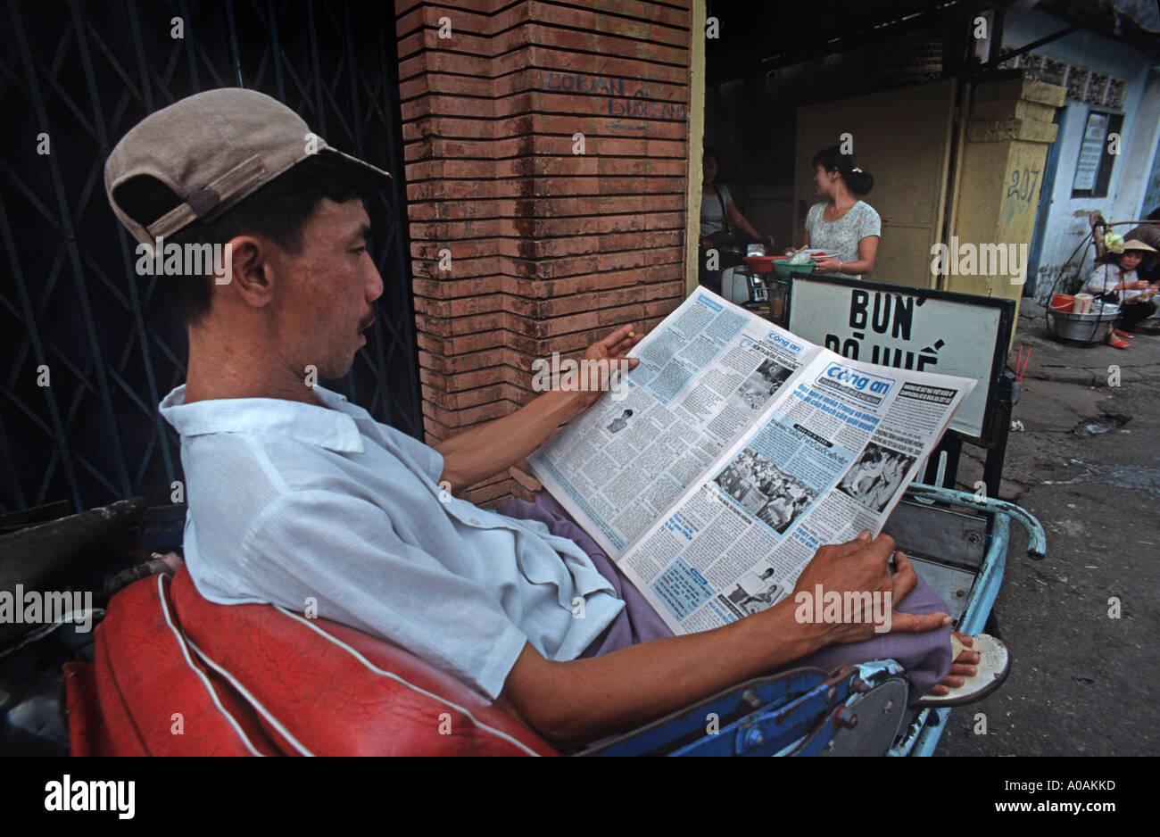 A rickshaw driver seated on his cycle reading a daily newspaper Ho Chi Minh City Saigon Vietnam - Stock Image