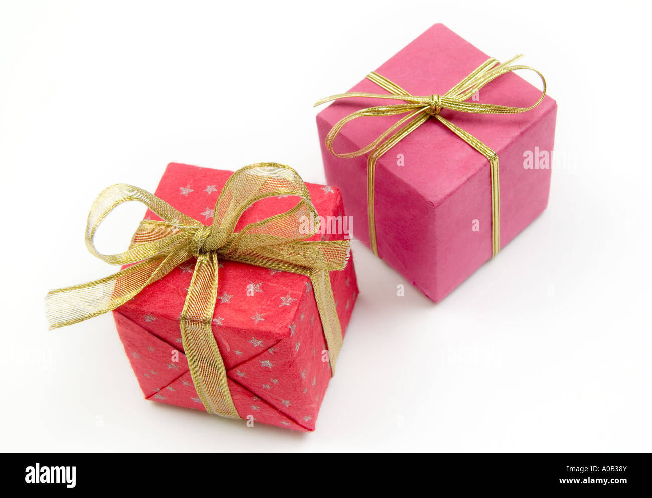 white background; cut out;  parcel; package; present; gift wrapped; bow; gold braid; surprise; wrap; christmas box - Stock Image