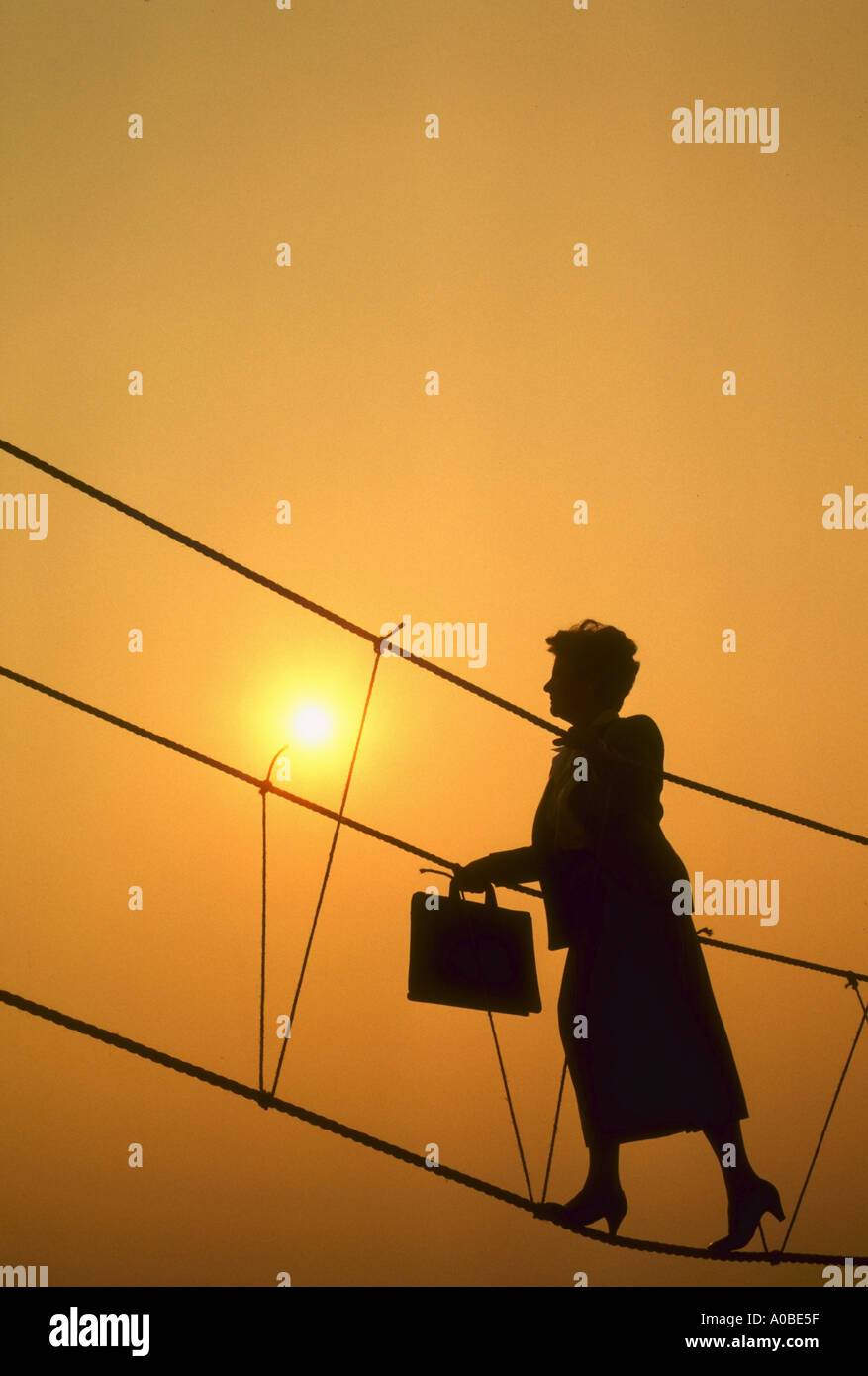 Rope ladder climbing to success This situation is also available with a man or with a younger woman - Stock Image