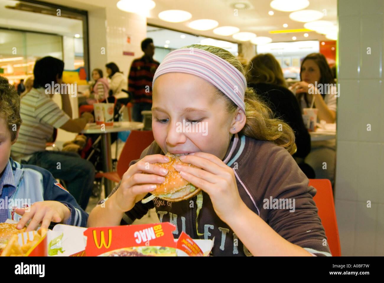 Child eating McDonald's Big Mac hamburger England UK - Stock Image