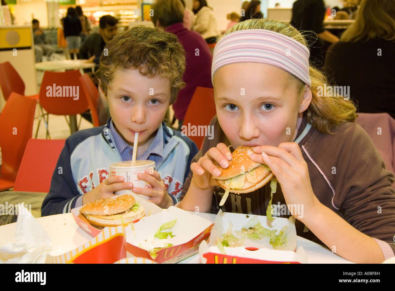 Children eating McDonald's Big Mac hamburgers England UK - Stock Image