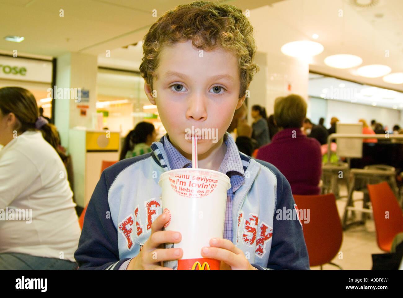 Child drinking McDonald's soft drink, England UK - Stock Image