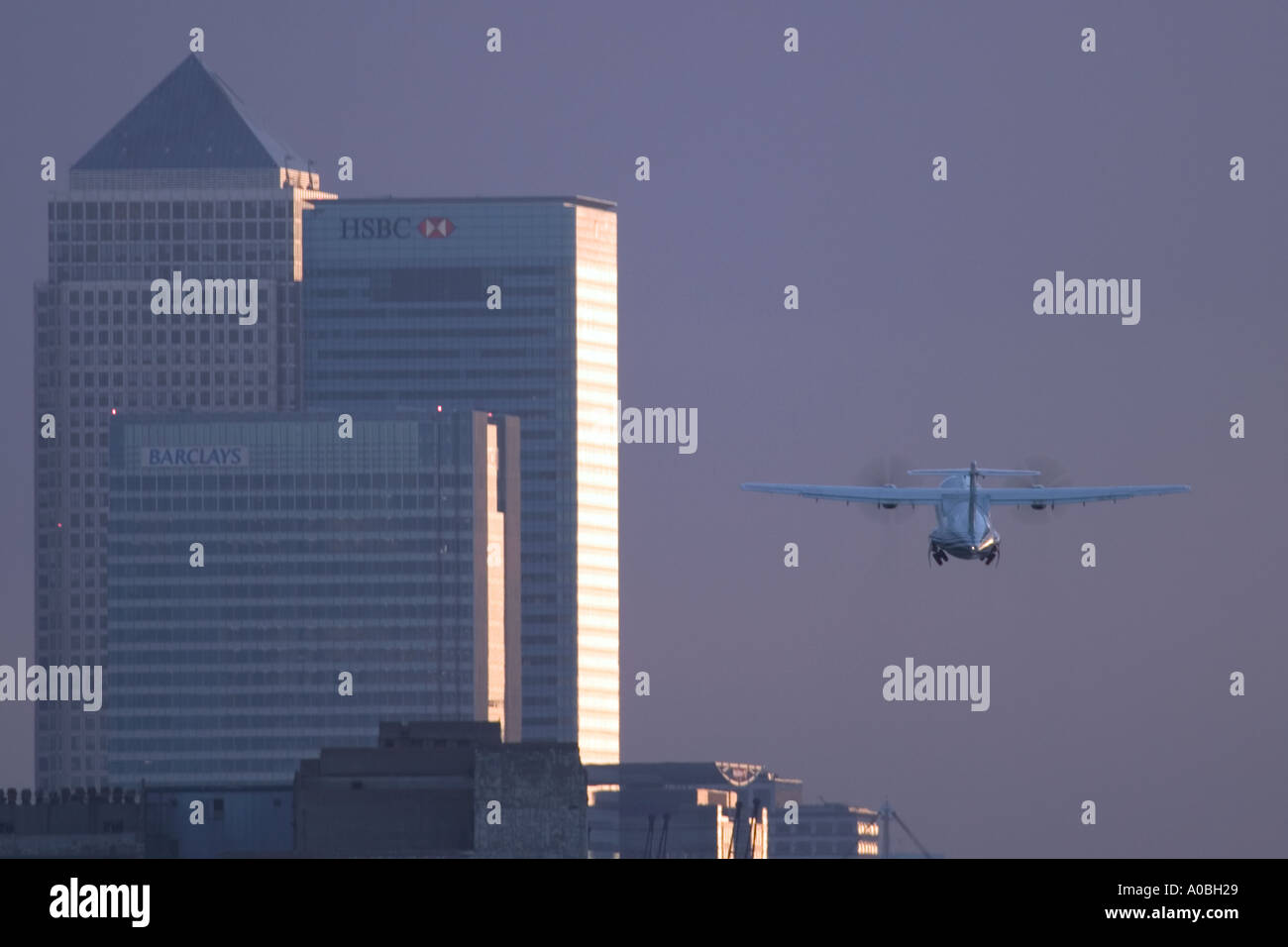 Airplane taking off at London City Airport with Canary Wharf in the background - Stock Image