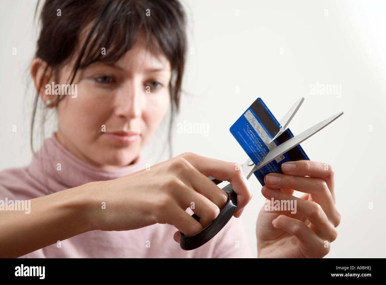 Young woman cutting up credit card with scissors, England UK - Stock Image