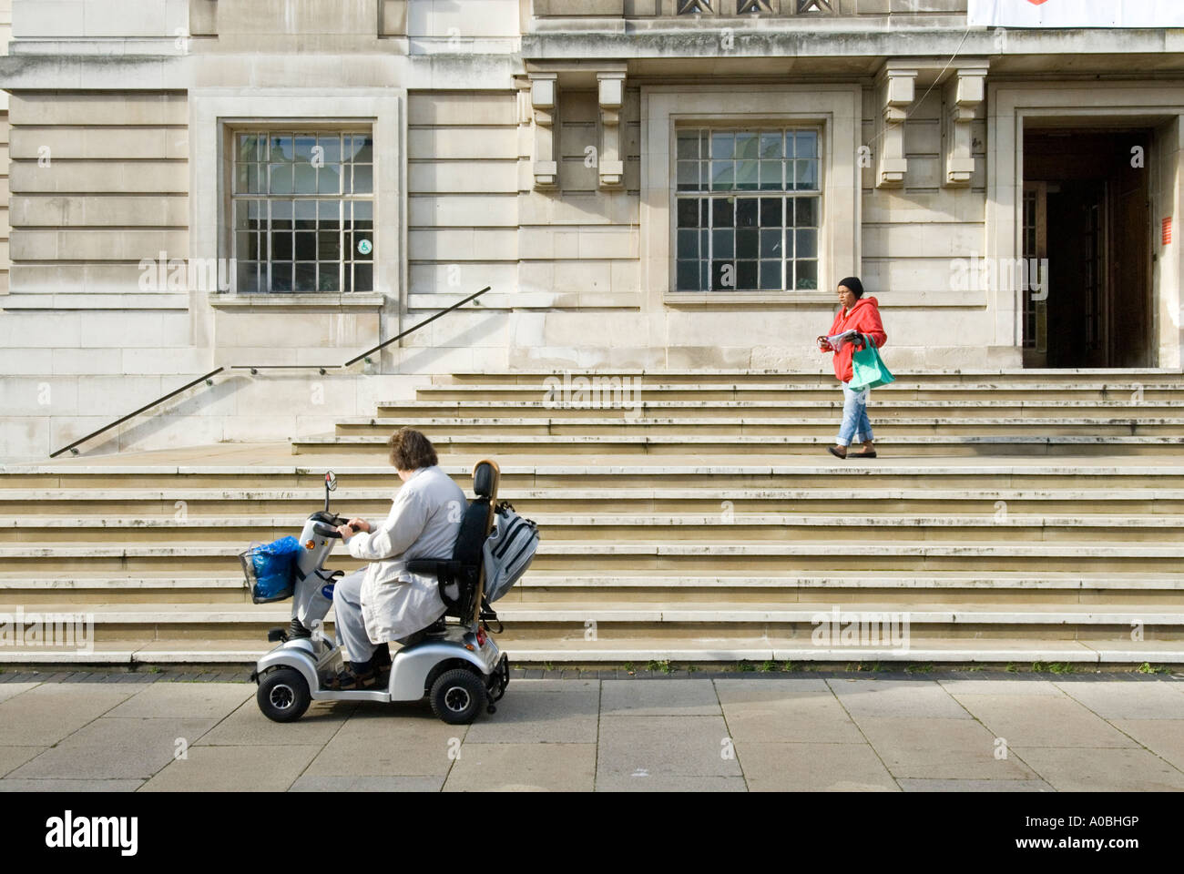 Woman in mobility scooter at foot of steps of Hackney Town Hall, London, England UK - Stock Image