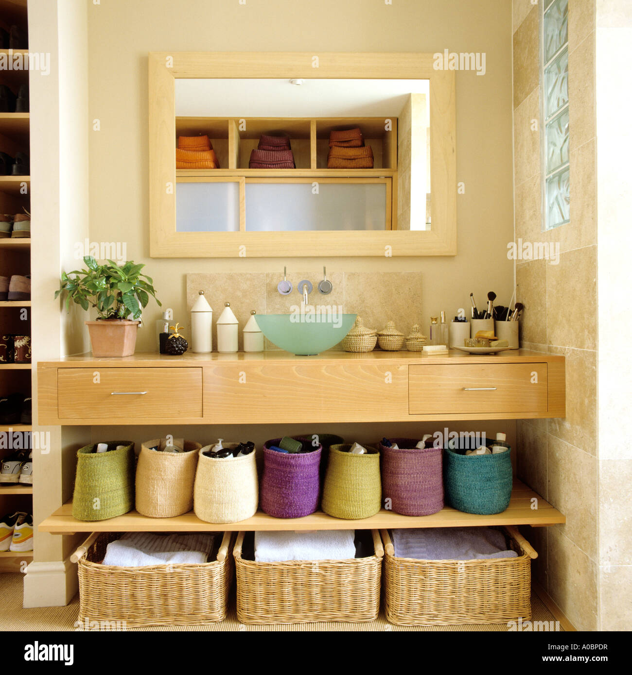 Contemporary bathroom in London with wicker storage baskets - Stock Image