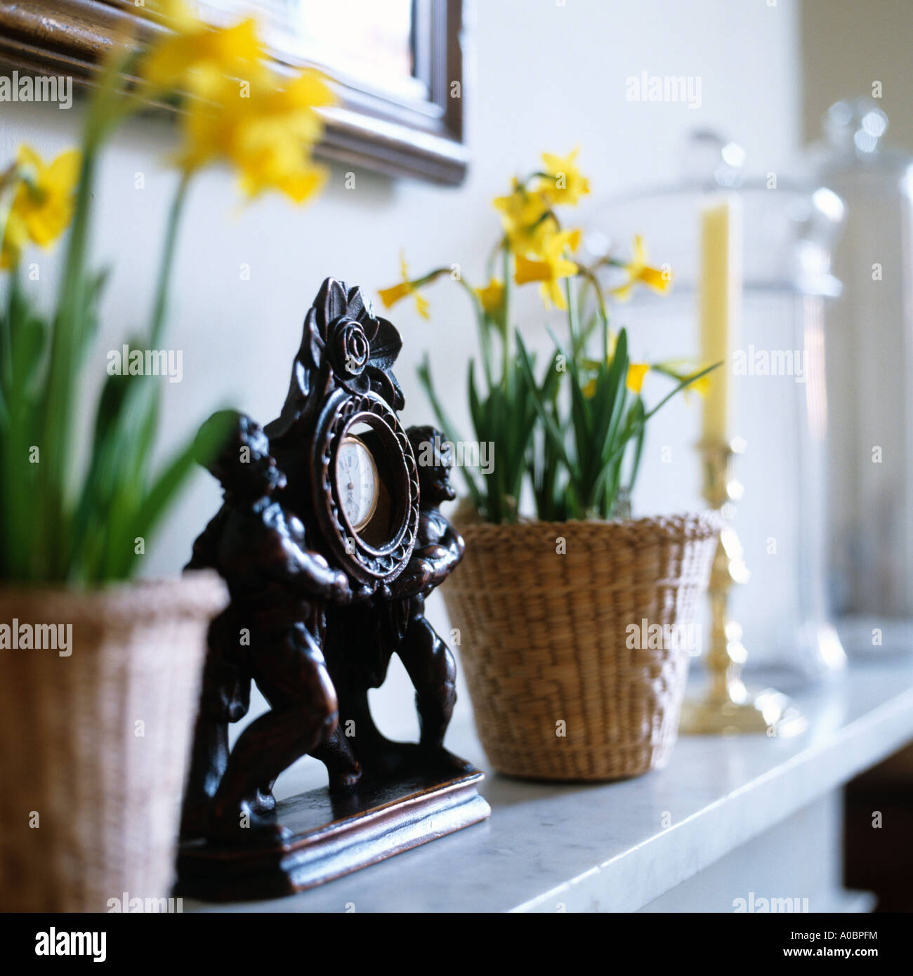 Daffodils in baskets on mantelpiece with clock - Stock Image