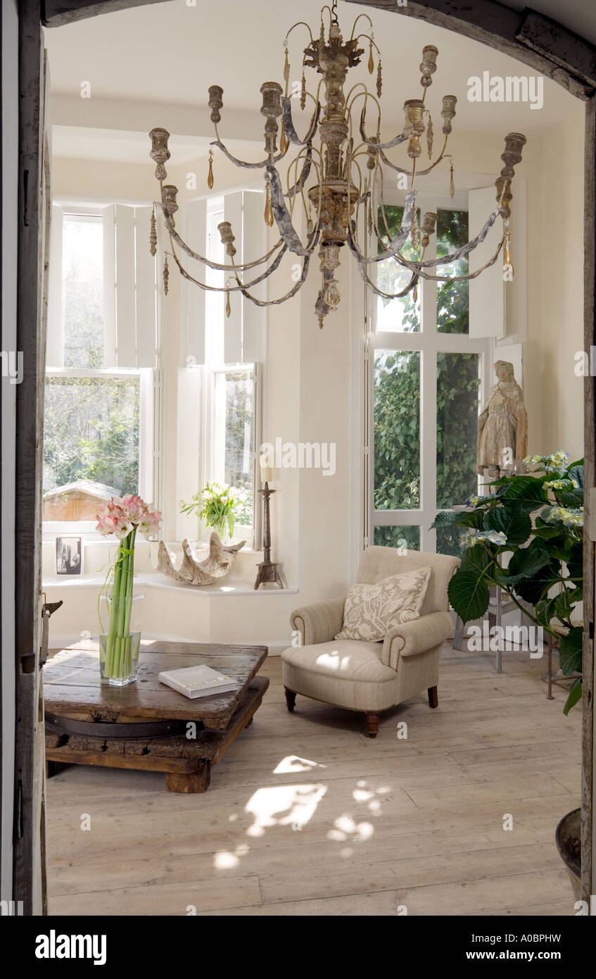 room view of white London interior with scrubbed timber floor and old French wooden chandelier - Stock Image