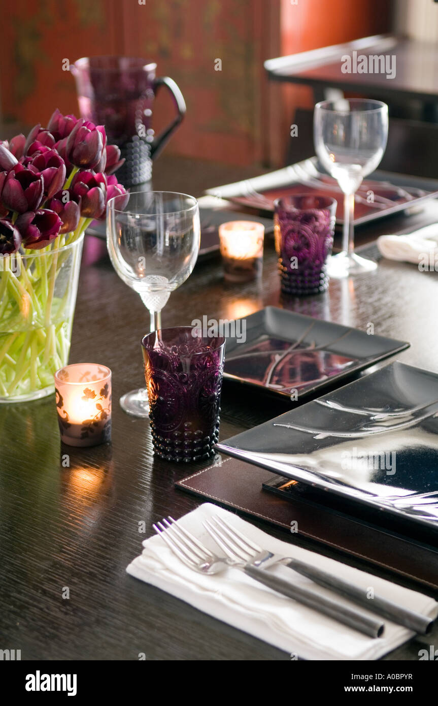 modern table setting with square plates, tealights and purple tulips ...