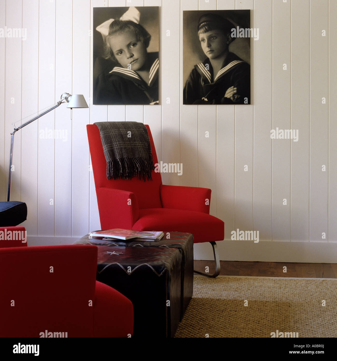 Sitting room with red armchairs and vintage sepia photographs on wall - Stock Image