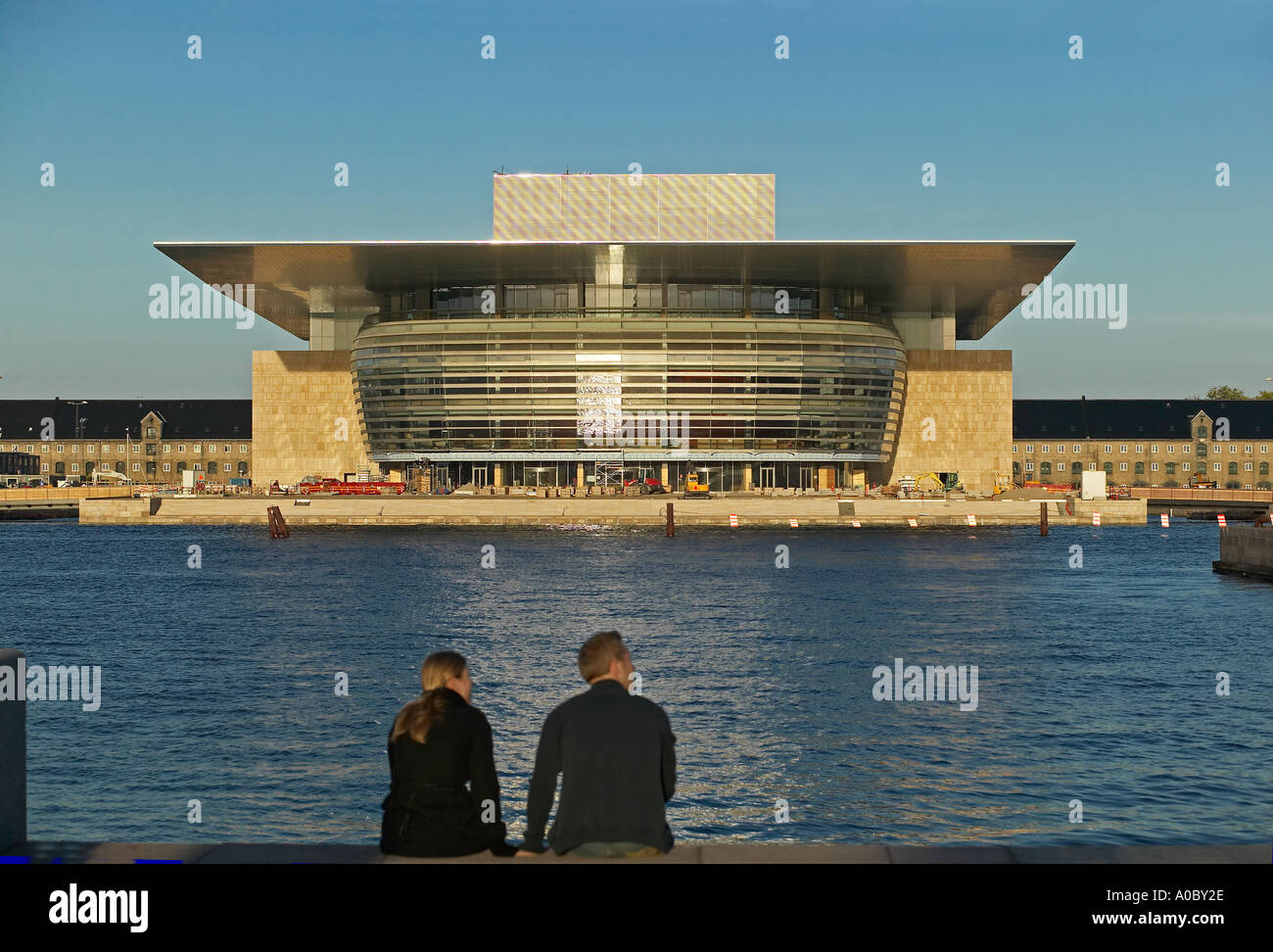 Couple in front of opera house building at sunset, Copenhagen, Denmark Europe - Stock Image