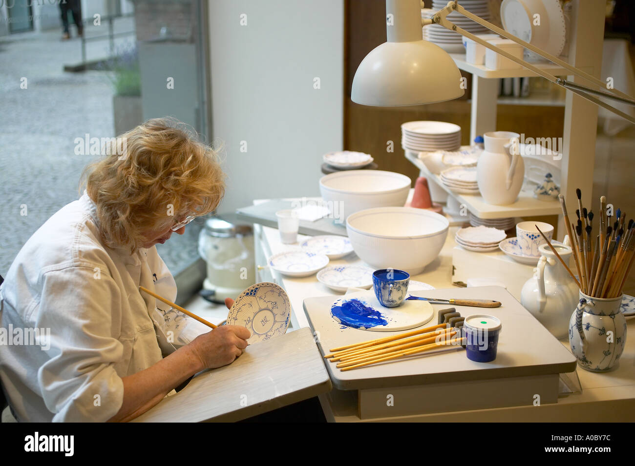 Woman painting a plate at 'Royal Copenhagen Porcelain' factory shop, Copenhagen, Denmark, Europe, - Stock Image
