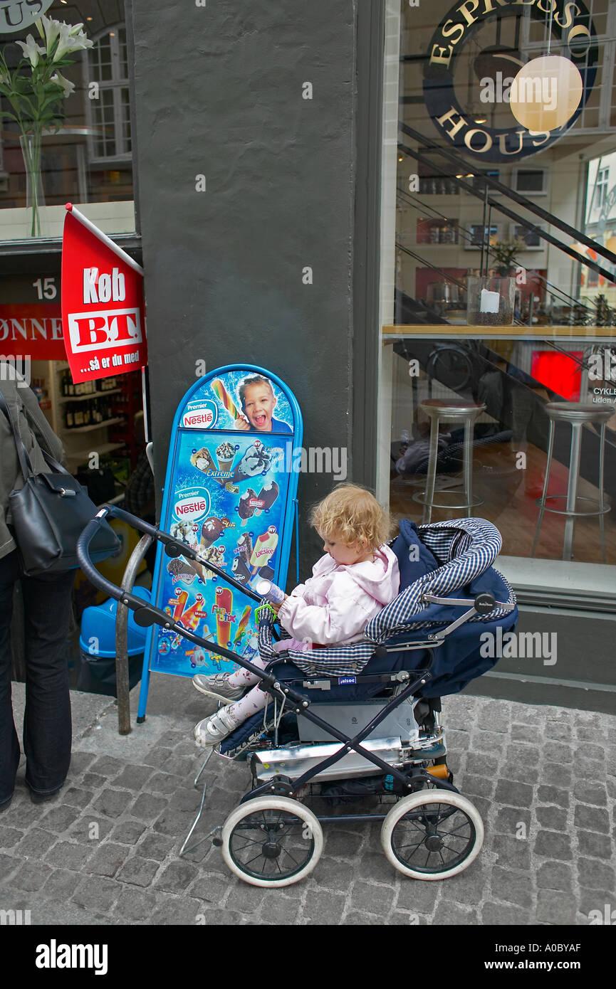 Little girl in pushchair, Strøget shopping street, Copenhagen, Denmark, Europe - Stock Image