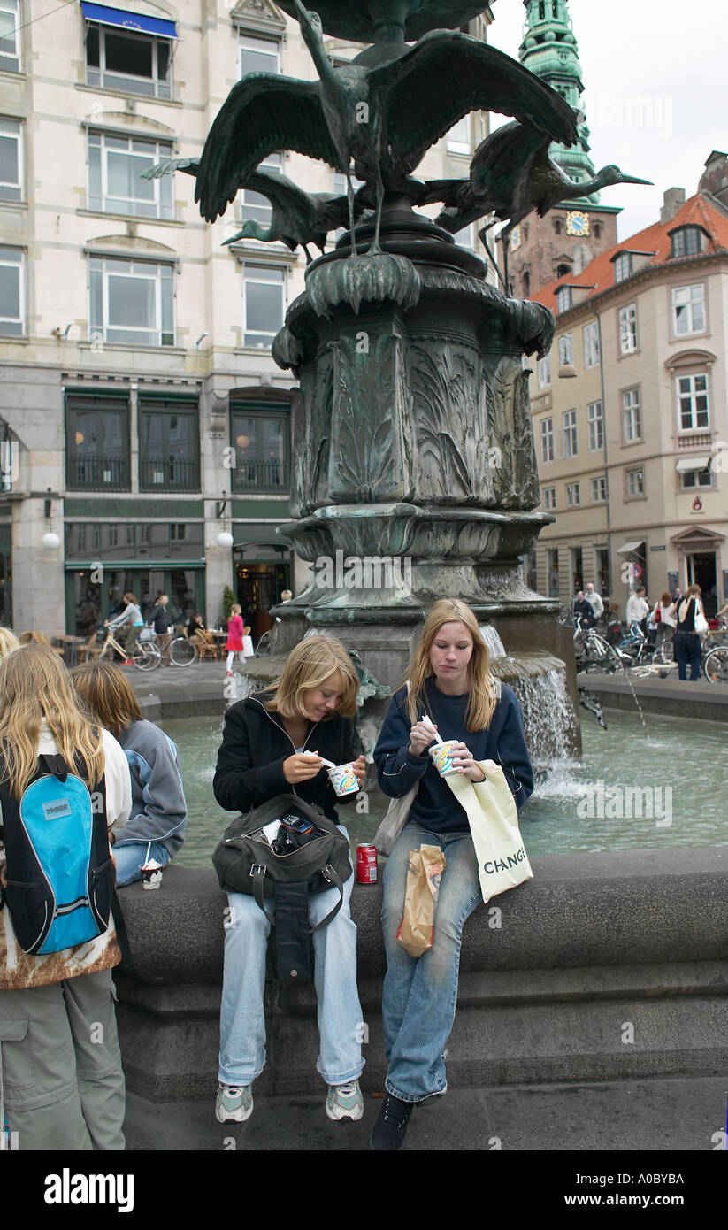 2 girls eating ice creams in front of  fountain of storks, 'Amagertorv' square, Copenhagen, Denmark, Europe - Stock Image