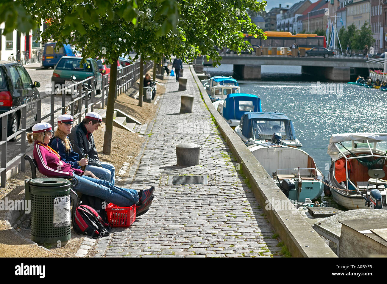 Danish students relaxing on bench at Christianhavn canal, Copenhagen, Denmark - Stock Image