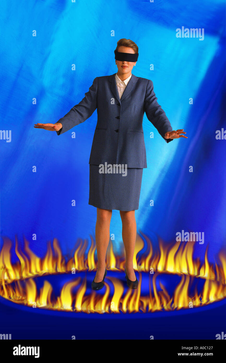 Blindfolded businesswoman standing in ring of fire - Stock Image