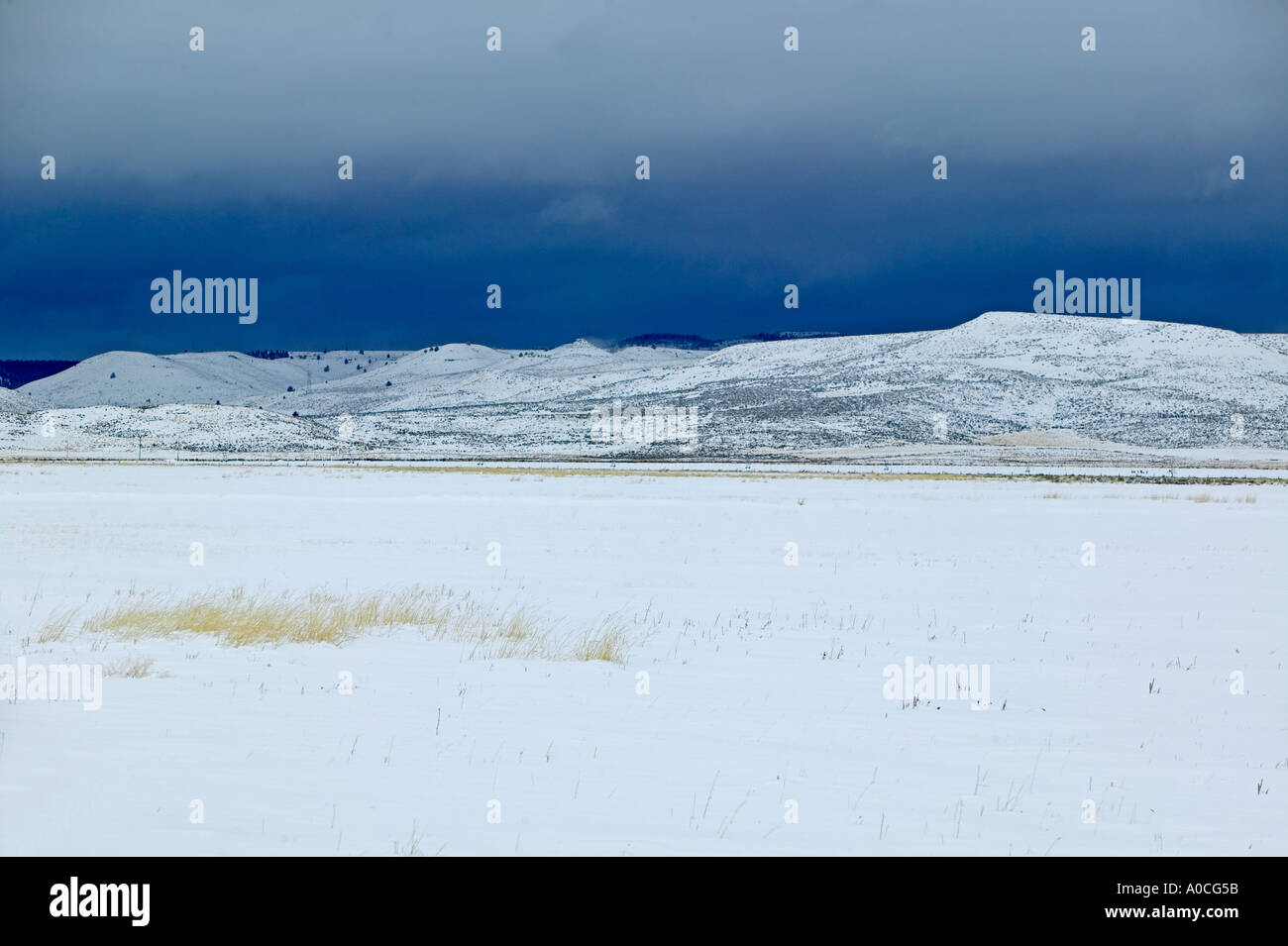 Snow covered hill with storm in back Near Burns Oregon - Stock Image