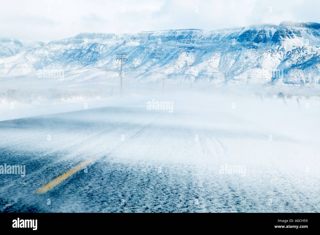 Blowing snow and road with Hart Mountain Warner Valley Oregon - Stock Image