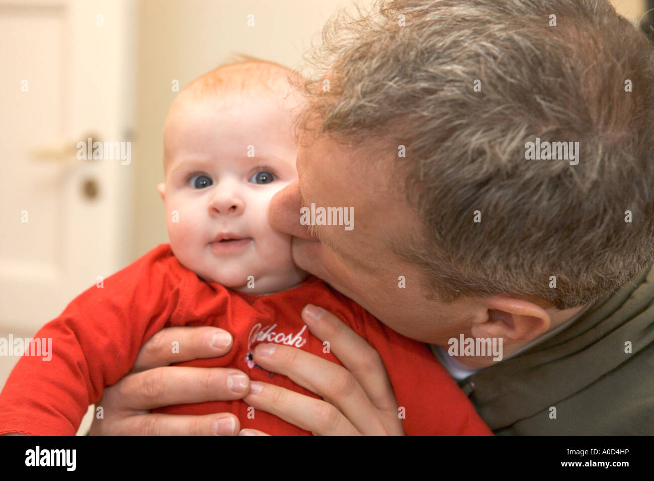 FATHER PLAYING WITH HIS BABY - Stock Image