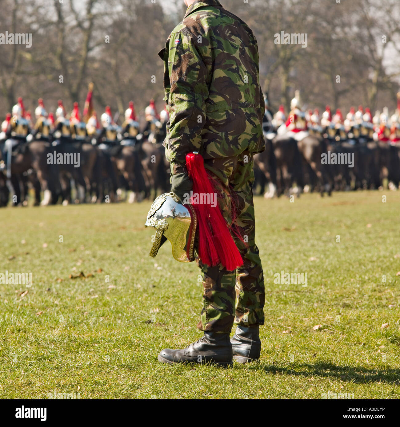 A British soldier holding a discarded helmet from a Household cavalry horseman in Hyde park London England Stock Photo